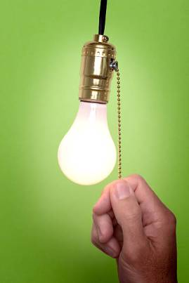 Hanging light bulb with pull switch.  Person is turning on or off the light.
