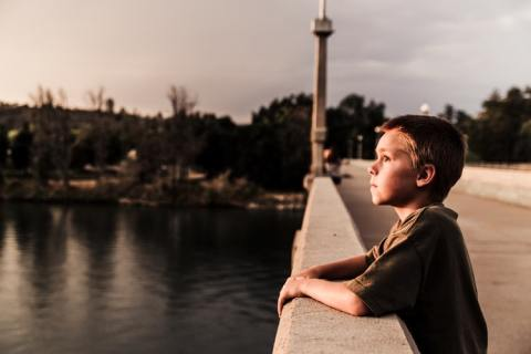 Boy looking on bridge