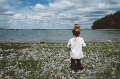 Child standing by lake